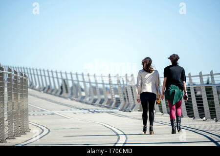 Two girls talk animatedly while walking along Tilikum Crossing bridge combining pleasant conversations with each other with useful exercise in walking - Stock Photo