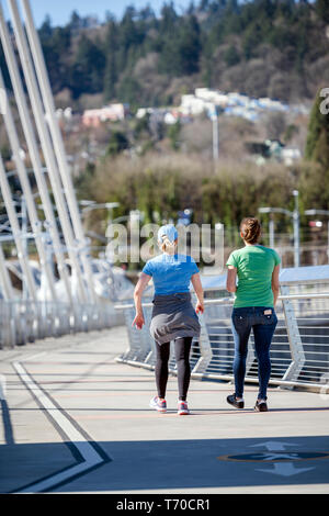 Two women talk animatedly while walking along Tilikum Crossing bridge combining pleasant conversations with each other with useful exercise in walking - Stock Photo