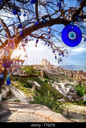 Uchisar castle at sunset and tree with traditional Turkish eyes amulets in Cappadocia - Stock Photo