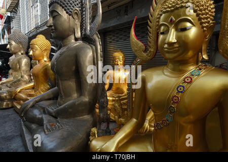 Buddha statues outside a factory for religious objects in Bamrung Muang Road, Bangkok, Thailand - Stock Photo