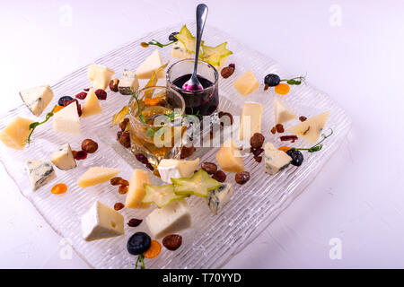 Cheeses with organic cheeses, fruits, nuts and jam on white background. Tasty cheese starter. - Stock Photo