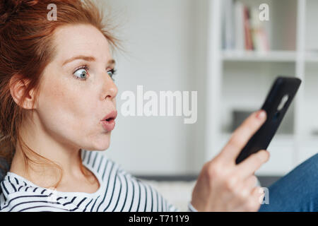Shocked young redhead woman reacting in amazement to news on her phone staring wide eyed at the screen with lips pursed exclaiming in a close up cropp - Stock Photo