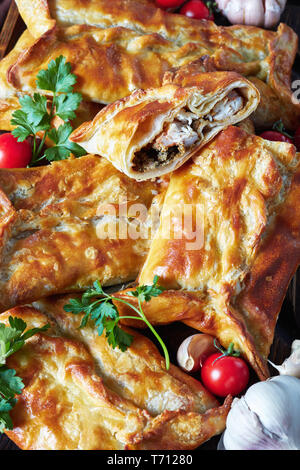 Chicken and ground walnut Stuffed Puff Pastry Borek,  Baked Chicken Pies sliced on a cutting board with tomato sauce on a table, georgian cuisine, ver - Stock Photo