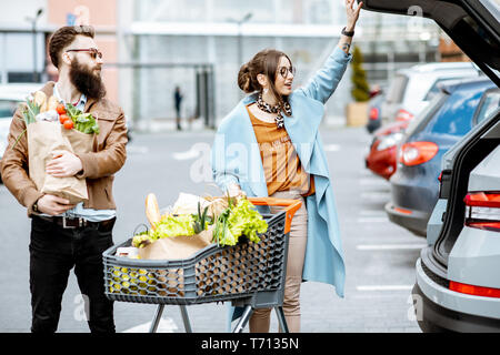 Young couple with shopping bags and cart full of fresh food on the outdooor parking near the supermarket - Stock Photo