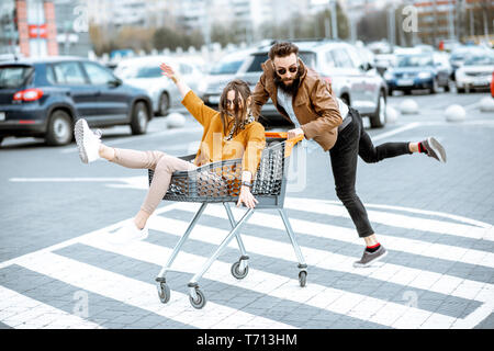 Young stylish coupe having fun riding with shopping cart on the outdoor parking near the supermarket - Stock Photo