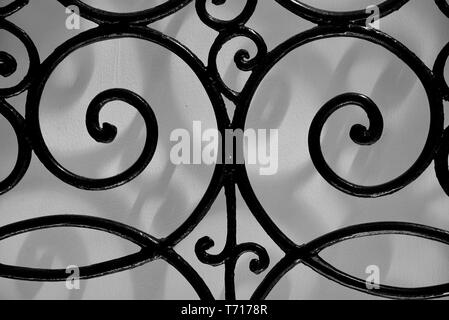 Curved black iron bars casting shadows on wall. - Stock Photo