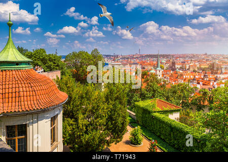 Prague red roofs and dozen spires of historical Old Town of Prague. Birds flying over red rooftops, spires and the Charles Bridge and Vltava River in  - Stock Photo