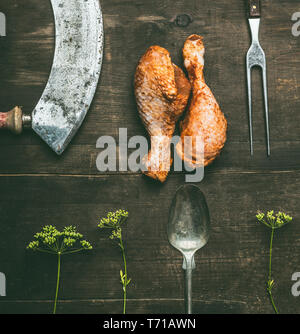 Raw barbecue marinated chicken drumstick with fresh herbs and kitchen utensils on rustic wooden background, top view. Grill preparation - Stock Photo