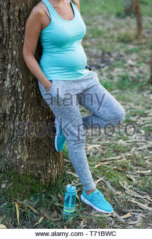 Detail of sporty pregnant woman taking a rest during outdoor healthy fitness workout in nature. - Stock Photo