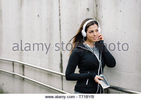 Urban fitness woman taking a workout rest for relaxing and listening music with headphones. - Stock Photo