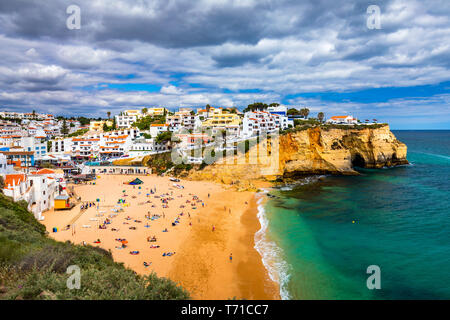 View of Carvoeiro fishing village with beautiful beach, Algarve, Portugal. View of beach in Carvoeiro town with colorful houses on coast of Portugal.  - Stock Photo