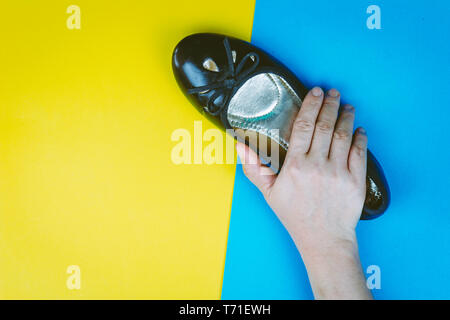 Woman hand holding black shoes on colourful background - Stock Photo