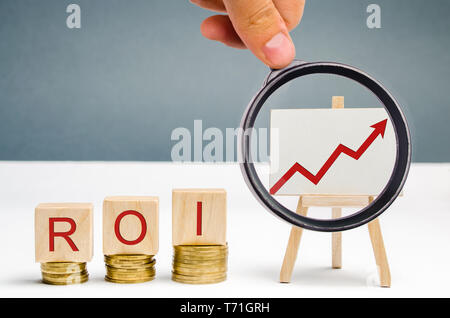 Wooden blocks with the word ROI and a poster with an arrow up. High level of business profitability. Return on investment, invested capital, rate. Suc - Stock Photo