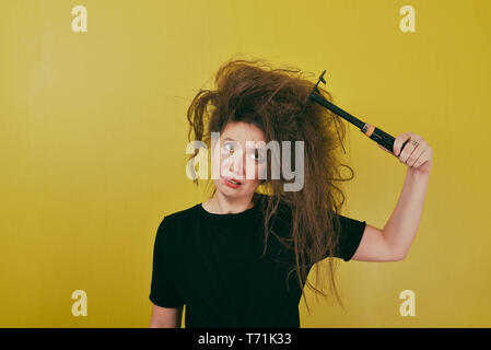 annoyed girl combs her hair  - Stock Photo