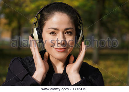 young woman listening to music with cordless headphones outside - Stock Photo