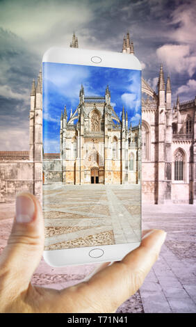Hand holding a smartphone with a picture of Batalha cathedral in Portugal (Europe) - 3D render concept image - Stock Photo