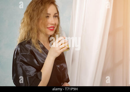 Portrait of young beautiful curly-haired woman in black housecoat looks out the window in the evening smiling and drinking juice, close-up