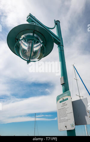 A green streetlight with a welcome sign towers over a dock at the marina in Kirkland, Washington. - Stock Photo