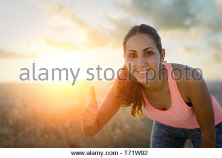 Successful female runner taking a rest during outdoor running workout at sunset. Female athlete doing success thumbs up geture. Sport and exercise mot - Stock Photo