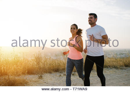 Two athletes running at sunset. Man and woman training together. - Stock Photo