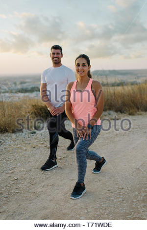 Young couple of athletes stretching legs or doing lunges exercises  for warming up before outdoor running workout. - Stock Photo