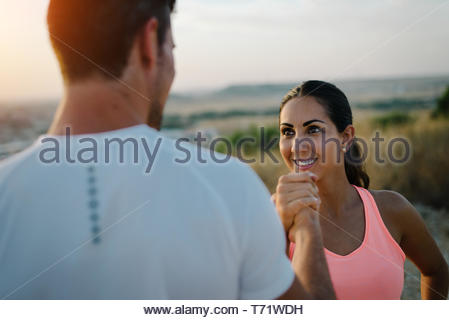 Couple of athletes giving high five for celebrating outdoor running workout goals and success. Man and woman training together. - Stock Photo