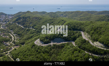 Curvy windy road between green mountain forest, top down aerial view. Summer landscape. - Stock Photo