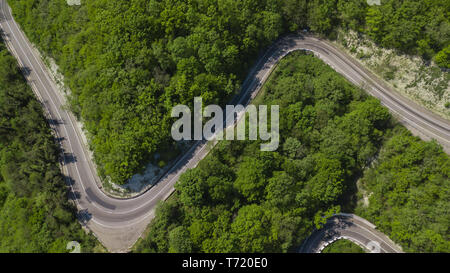 View from above of curvy windy road between green mountain forest. Summer landscape. - Stock Photo