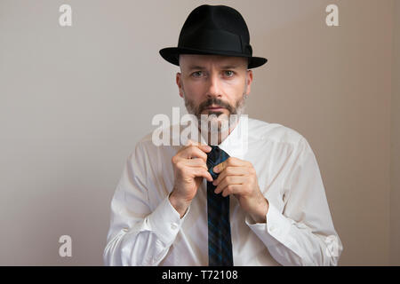 Adult man with hat and beard is knotting his necktie - Stock Photo