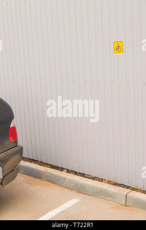 Reserved Parking sign for disabled small size on metal fence, accessible environment for people with disabilities. - Stock Photo