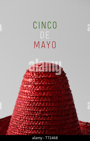 a red Mexican hat and the text Cinco de Mayo, May 5 in Spanish, a popular Mexican holiday that commemorates de victory at the Battle of Puebla, writte - Stock Photo
