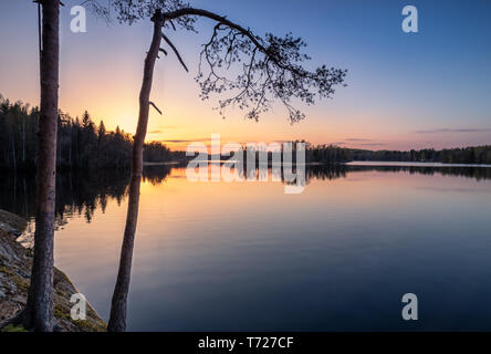 Scenic landscape with sunset, peaceful lake and tree roots at calm spring evening in Finland - Stock Photo