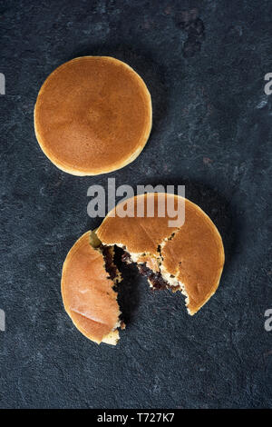 high angle view of two dorayaki, a pastry filled with adzuki bean paste typical of Japan, on an elegant black stone surface - Stock Photo