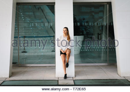 Confident young stylish professional woman taking a break outside corporate building. - Stock Photo