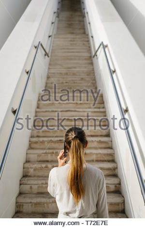 Business and professional success concept. Back view of a woman on mobile phone call towards long urban stairs. - Stock Photo
