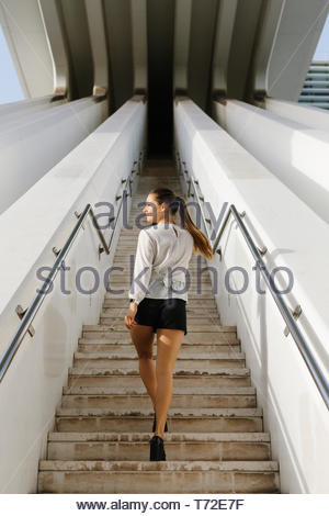 Young professional woman climbing stairs. Stylish business woman on cellphone call outside. - Stock Photo