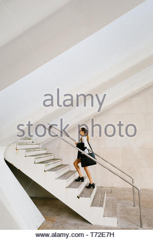 Young busy stylish professional woman going to her job carrying a coffee. - Stock Photo