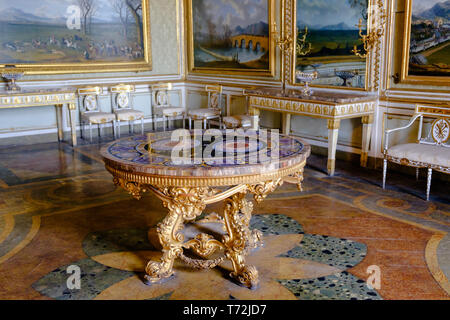 A neo-baroque table with a hard stone table-top stands in a royal apartment of the 'Reggia di Caserta'. Paintings and furniture complete the richness. - Stock Photo