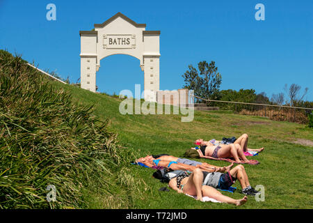The Bondi beach to Coogee walk is a coastal walk in Sydney New South Wales, Australia. Sunbath in Coogee beach Dolphins Point and Giles Baths - Stock Photo