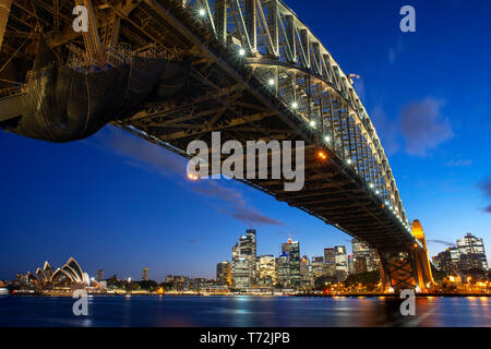 Side view of Sydney Harbour bridge Opera House and city CBD at sunset. Illuminated arch of the bridge reflecting in blurred waters Sydney, New South W - Stock Photo