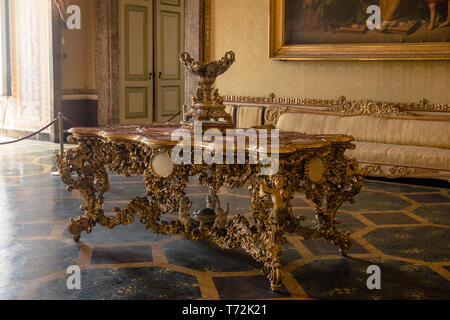 A table stands in of the huge halls of the 'Reggia di Caserta', a former royal palace that was the largest royal residence in the world. - Stock Photo