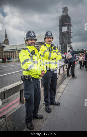 Two London policemen stand watch on Westminster Bridge, London, UK - Stock Photo