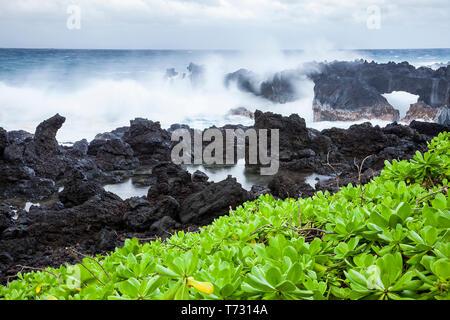 Waves from Pacific Ocean crashing against lave rock at Wai'anapapanapa State Park, Maui, Hawaii, USA - Stock Photo