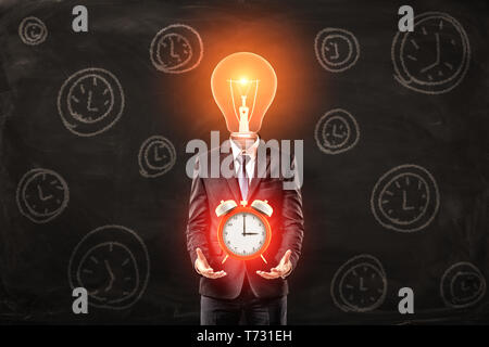 Man in suit with lightbulb instead head, levitating big red alarm clock above palms, standing against black wall with pattern of alarm clocks on it. - Stock Photo