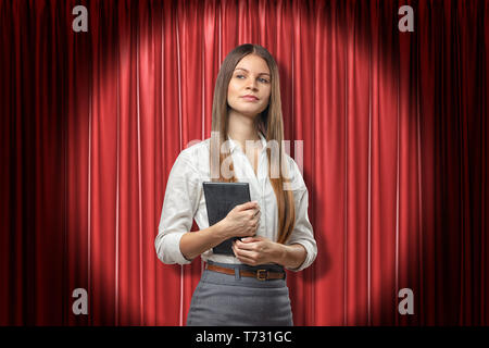 Front crop view of young attractive businesswoman holding daily planner standing in spotlight against red stage curtain. - Stock Photo