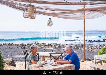 Successful retirement recreation, summer vacation concept. Retired mature couple enjoying a beautiful sunny day at the beach. Happy senior woman and m - Stock Photo