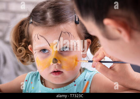 Painting The Face Of A Little Girls With Color Brush - Stock Photo