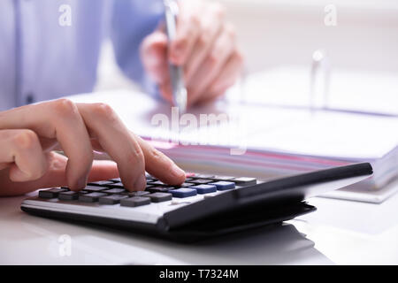 Businessman Using A Calculator To Calculate Invoice In Office - Stock Photo