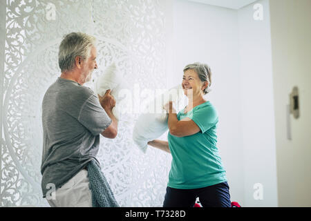 Happy cheerful old senior caucasian couple play at home with pillows in the bedroom - playful and youthful concept with no limit age to have fun and l - Stock Photo