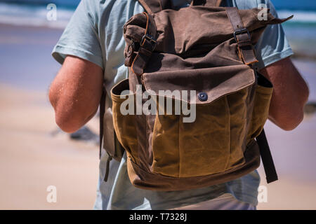 Travel and vacation lifestyle concept with man and leather vintage backpack viewed from rear - sku and beach in background for outdoor leisure activit - Stock Photo